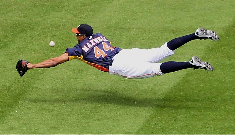 Houston Astros outfielder Justin Maxwell (44) dives for a fly ball during an MLB baseball game against the Oakland Athletics at Minute Maid Park on Sunday April 7, 2013 in Houston, Texas. (AP Photo/ The Courier, Jason Fochtman) Photo: Jason Fochtman, Associated Press