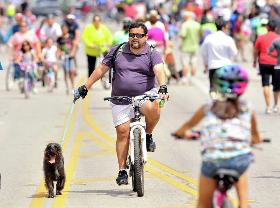 Arturo Ponce and his dog Dexter cruise along a closed Broadway St. Sunday during the 3rd annual Siclovia hosted by the city of San Antonio and the YMCA. Photo: Robin Jerstad, Express-News