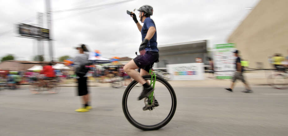 A unicyclist takes pictures while riding along a closed Broadway St. Sunday during the 3rd annual Siclovia event hosted by the city of San Antonio and the YMCA. Photo: Robin Jerstad, Express-News