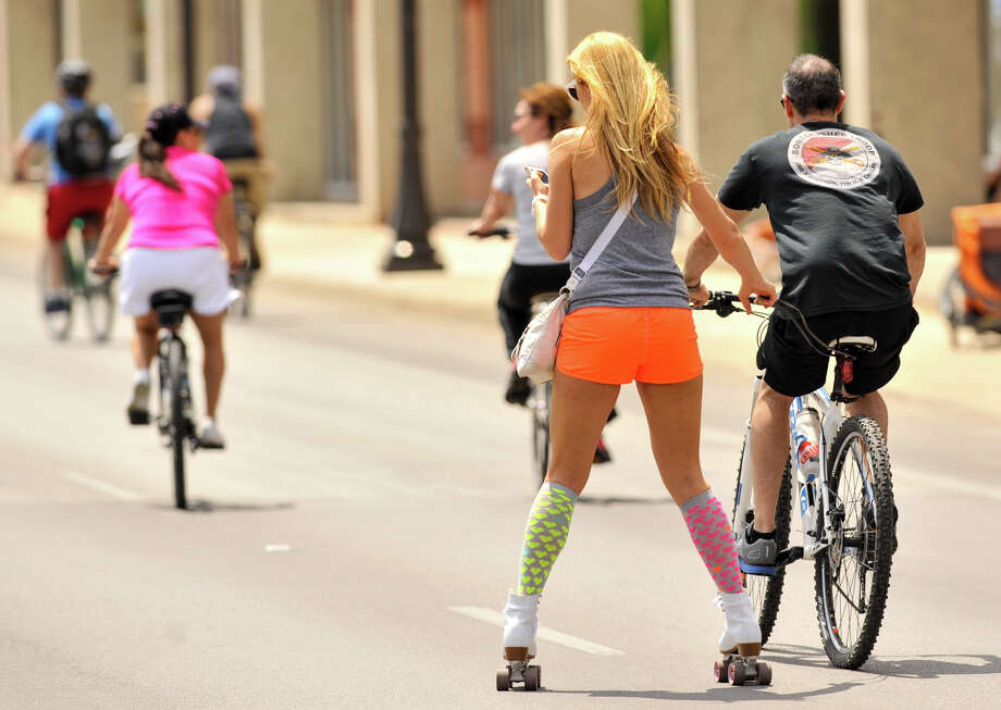 A roller skater is pulled along by a cyclist during Sunday's Siclovia event on Broadway St. which was closed to traffic. The event was hosted by the city of San Antonio and the YMCA. Photo: Robin Jerstad, Express-News
