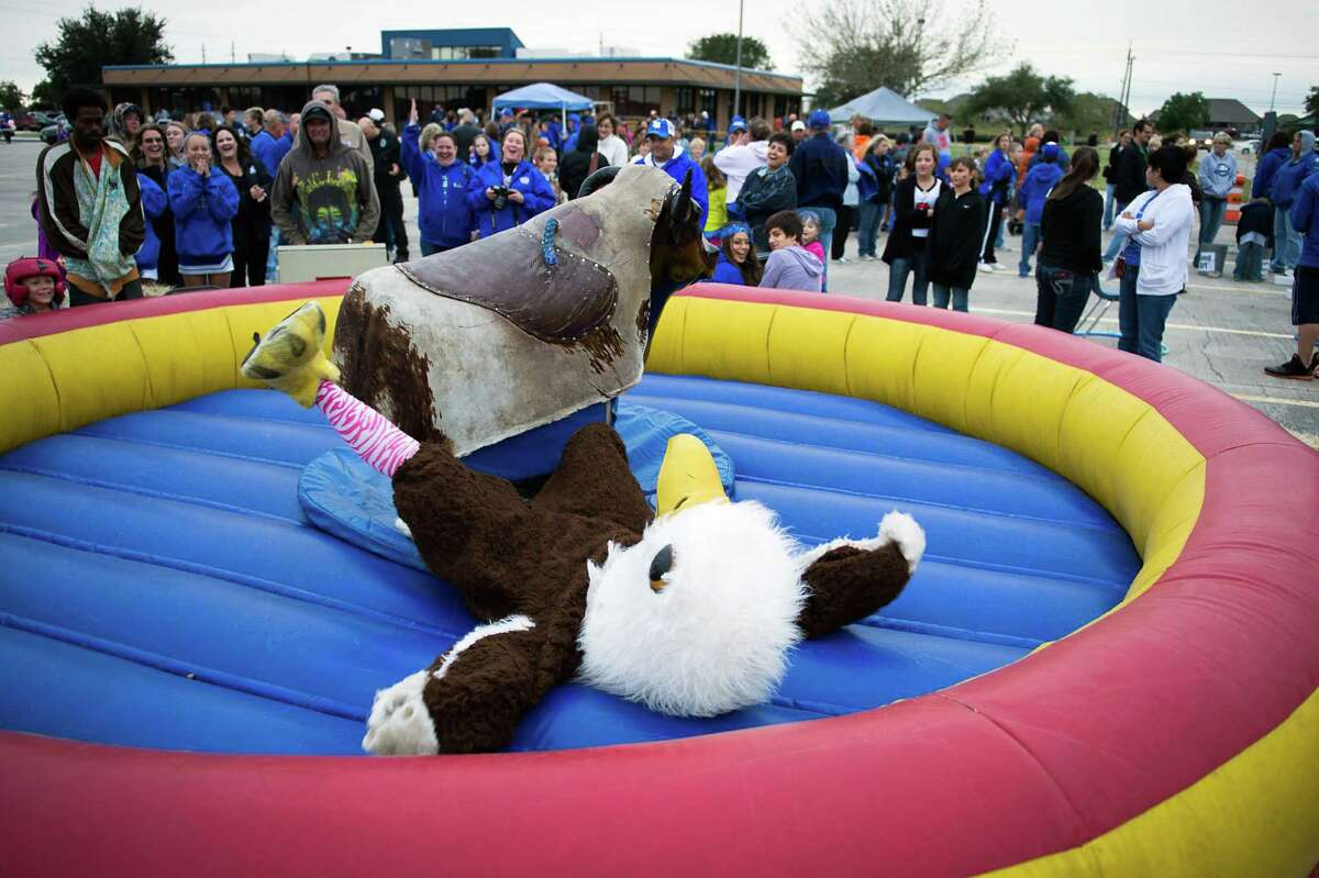The Barbers Hill Eagles mascot takes a tumble from a mechanical bull during a pre game tailgate party before a high school football game between Barbers Hill and Dayton at Eagle Stadium, Friday, Oct. 26, 2012, in Mont Belvieu.
