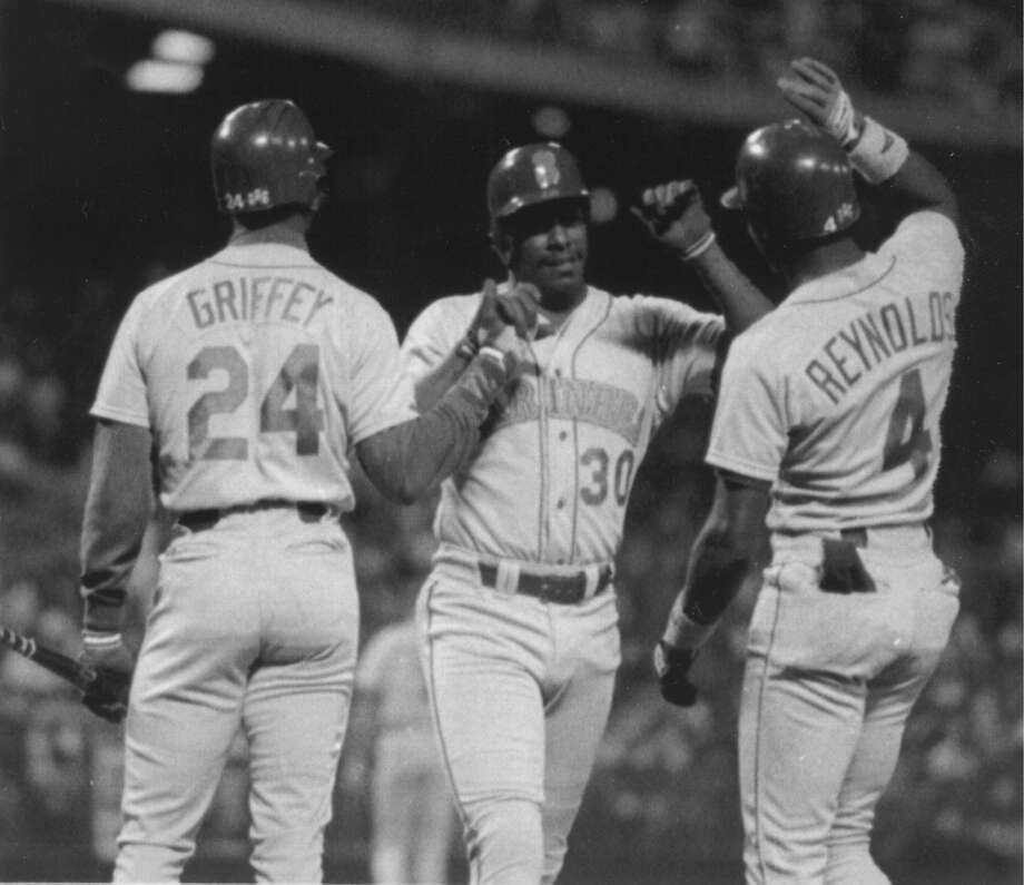 April 13, 1990 -- Oakland Athletics 15, Mariners 7 54,874 attendance, fourth game of the season.Maybe scheduling the home opener for Friday the 13th was unlucky, because the M's trailed this one big from the beginning. Seattle starter Scott Bankhead lasted only 1 1/3 innings and the A's slapped 21 hits around the Kingdome.Photo:  Ken Griffey Sr., center, is greeted at home plate by his son, Ken Jr., and Harold Reynolds in this undated pic from 1990. Photo: Seattle P-I Archives