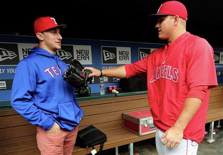 Johnny Manziel, left, Heisman Trophy winner and Texas A&M quarterback, talks with Los Angeles Angels center fielder Mike Trout in the dugout during warmups before a baseball game between the Angels and the Texas Rangers, Sunday, April 7, 2013, in Arlington, Texas. Photo: LM Otero, AP / AP