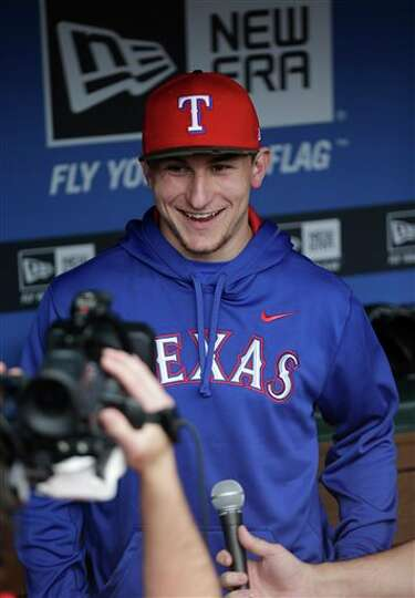 Heisman Trophy winner Texas A&M quarterback Johnny Manziel tapes a promo in the dugout during warm-u