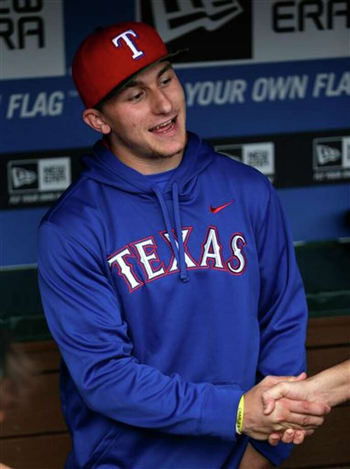 Heisman Trophy winner Texas A&M quarterback Johnny Manziel shakes hands in the dugout during warm-ups before a baseball game between the Los Angeles Angels and Texas Rangers Sunday, April 7, 2013, in Arlington, Texas. Manziel is on hand to throw out the first pitch. Photo: LM Otero, AP / AP