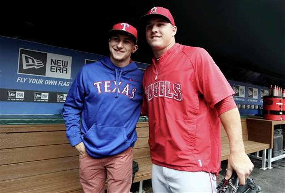 Johnny Manziel, left, Heisman Trophy winner and Texas A&M quarterback, poses for a photo with Los Angeles Angels center fielder Mike Trout in the dugout during warmups before a baseball game between the Angels and the Texas Rangers, Sunday, April 7, 2013, in Arlington, Texas. Photo: LM Otero, AP / AP