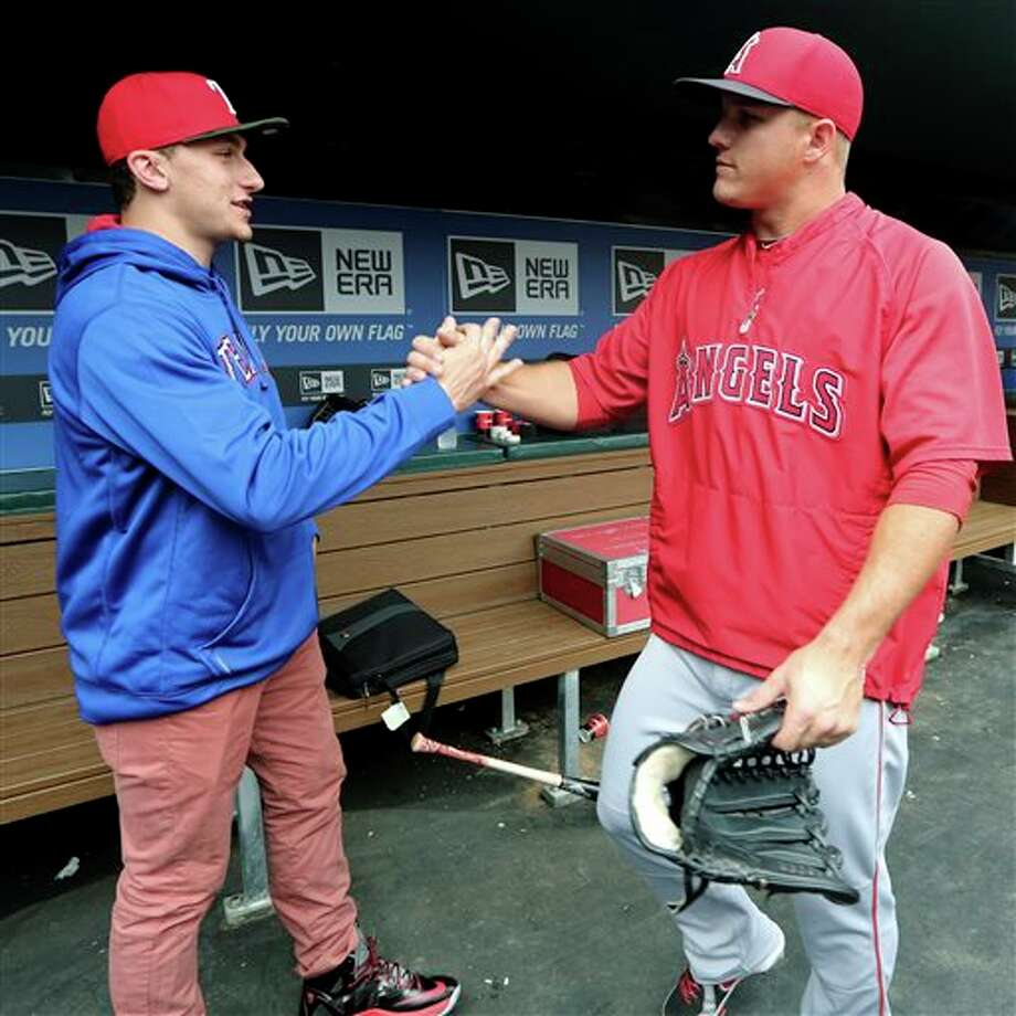 Johnny Manziel, left, Heisman Trophy winner and Texas A&M quarterback, shakes hands with Los Angeles Angels center fielder Mike Trout in the dugout during warmups before a baseball game between the Angels and the Texas Rangers, Sunday, April 7, 2013, in Arlington, Texas. Photo: LM Otero, AP / AP