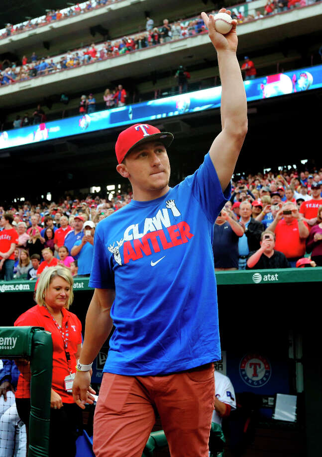Johnny Manziel, Heisman Trophy winner and Texas A&M quarterback, waves as he takes the field to throw out the ceremonial first pitch before a baseball game between the Los Angeles Angels and Texas Rangers, Sunday, April 7, 2013, in Arlington, Texas. (AP Photo/LM Otero) Photo: LM Otero, Associated Press / AP