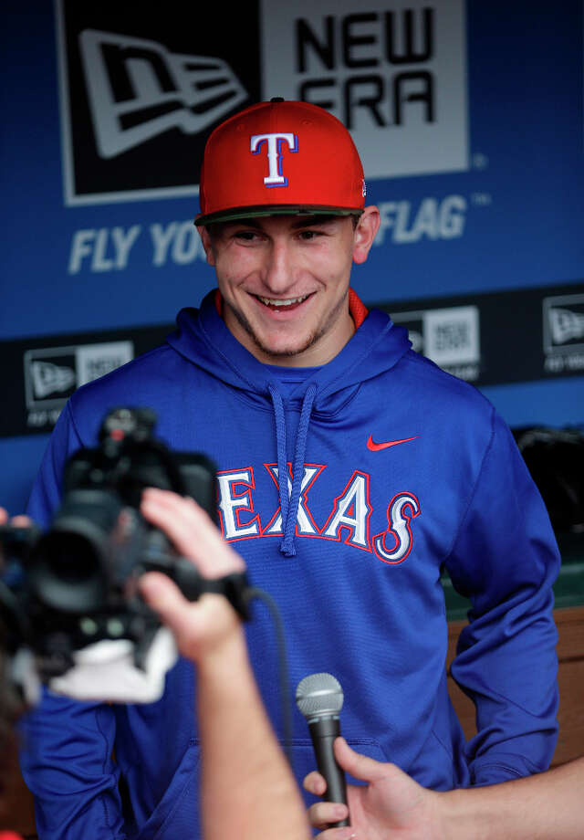 Heisman Trophy winner Texas A&M quarterback Johnny Manziel tapes a promo in the dugout during warm-ups before a baseball game between the Los Angeles Angels and Texas Rangers Sunday, April 7, 2013, in Arlington, Texas. Manziel is on hand to throw out the first pitch.  (AP Photo/LM Otero) Photo: LM Otero, Associated Press / AP