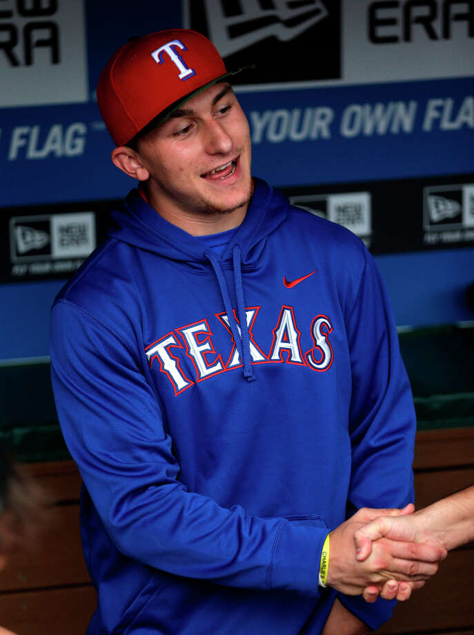 Heisman Trophy winner Texas A&M quarterback Johnny Manziel shakes hands in the dugout during warm-ups before a baseball game between the Los Angeles Angels and Texas Rangers Sunday, April 7, 2013, in Arlington, Texas. Manziel is on hand to throw out the first pitch.  (AP Photo/LM Otero) Photo: LM Otero, Associated Press / AP