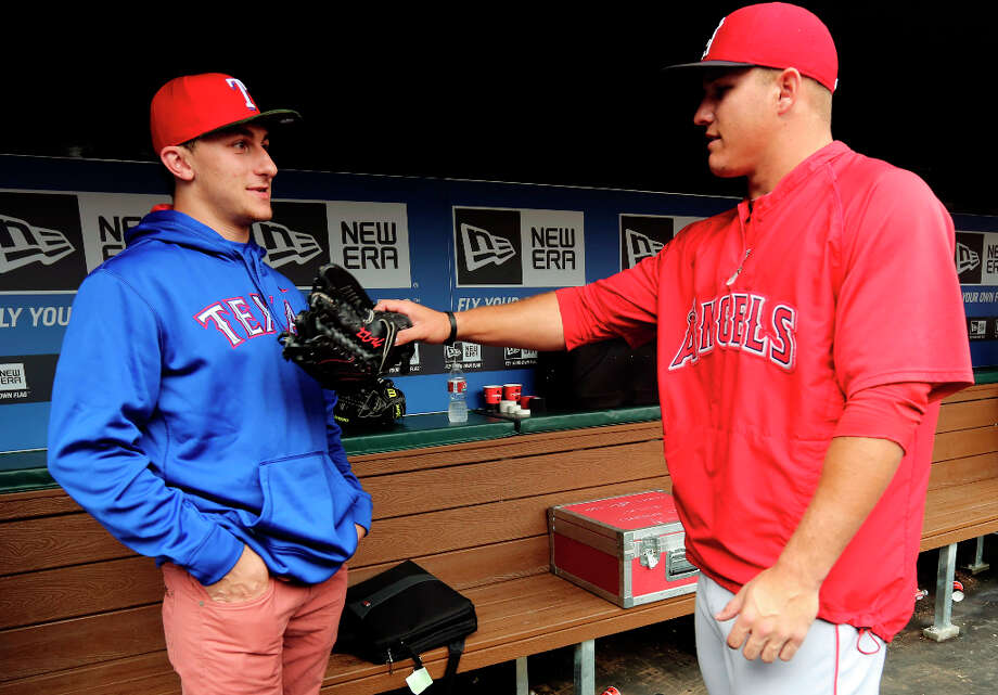 Johnny Manziel, left, Heisman Trophy winner and Texas A&M quarterback, talks with Los Angeles Angels center fielder Mike Trout in the dugout during warmups before a baseball game between the Angels and the Texas Rangers, Sunday, April 7, 2013, in Arlington, Texas. (AP Photo/LM Otero) Photo: LM Otero, Associated Press / AP
