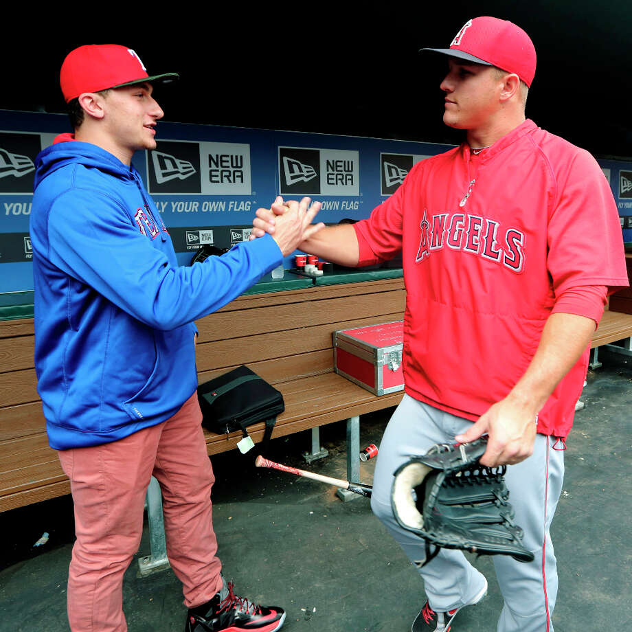 Johnny Manziel, left, Heisman Trophy winner and Texas A&M quarterback, shakes hands with Los Angeles Angels center fielder Mike Trout in the dugout during warmups before a baseball game between the Angels and the Texas Rangers, Sunday, April 7, 2013, in Arlington, Texas. (AP Photo/LM Otero) Photo: LM Otero, Associated Press / AP