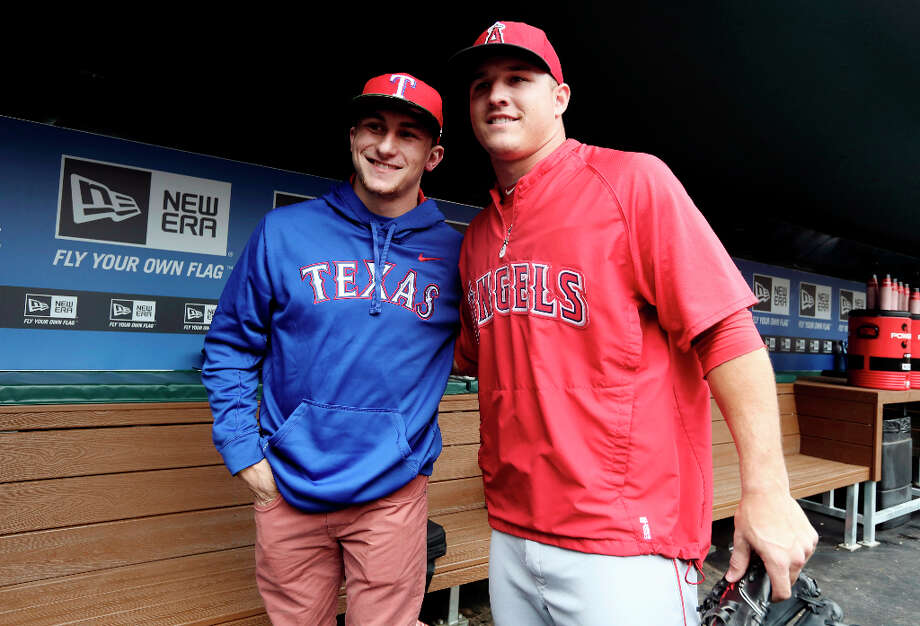 Johnny Manziel, left, Heisman Trophy winner and Texas A&M quarterback, poses for a photo with Los Angeles Angels center fielder Mike Trout in the dugout during warmups before a baseball game between the Angels and the Texas Rangers, Sunday, April 7, 2013, in Arlington, Texas. (AP Photo/LM Otero) Photo: LM Otero, Associated Press / AP