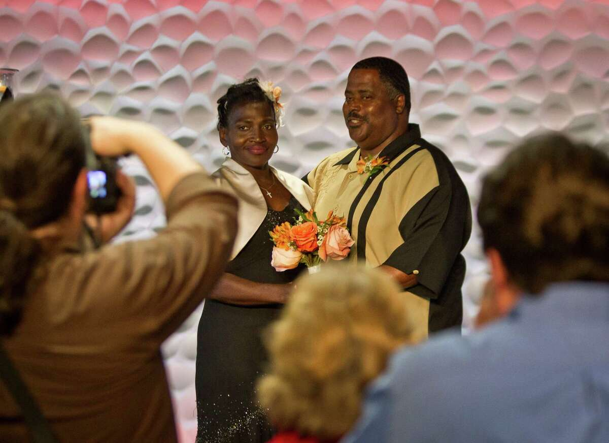 Wanda Ware and her new husband, Bryan Prejean, pose for wedding photos Sunday in Houston First Baptist's downtown campus. The couple were once homeless and attended bible class at the church.