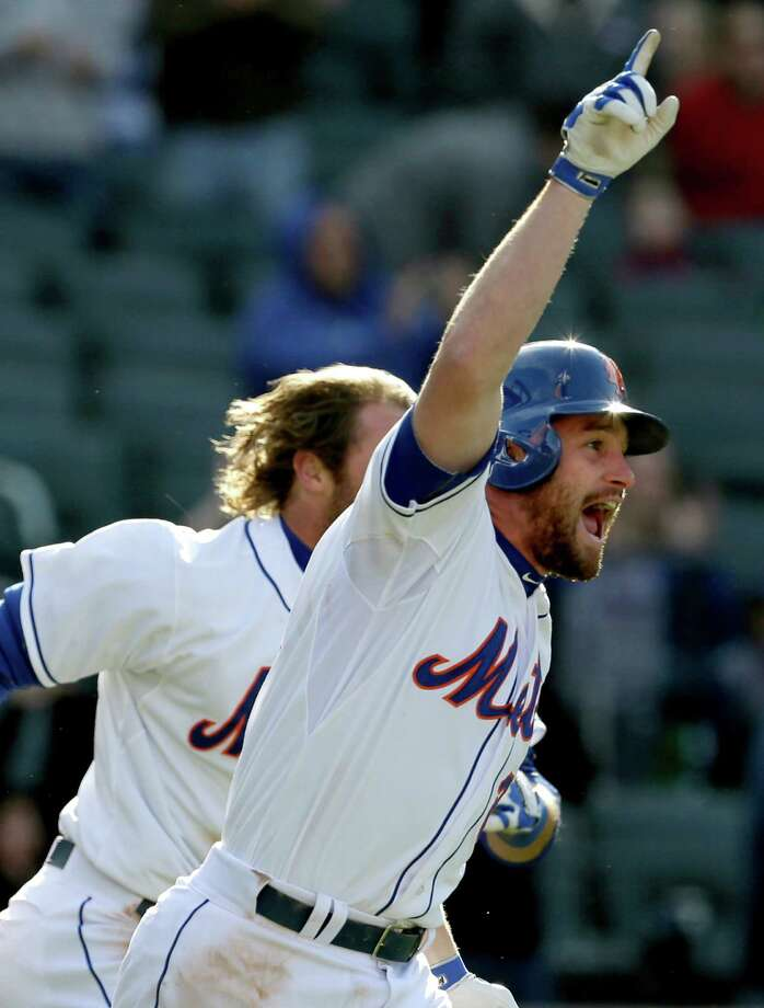 New York Mets' Daniel Murphy celebrates as he runs to greet teammate Marlon Byrd, who hit a walk-off, two-run single, during the ninth inning of a baseball game at CitiField, Sunday, April 7, 2013, in New York. The Mets won 4-3. (AP Photo/Seth Wenig) Photo: Seth Wenig