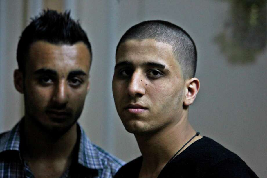 Ayman al-Sayed, 19, right, with his hair cut, and his friend Mohammed Hanouna, 18, left, pose for photo during an interview in Gaza City, Sunday, April 7, 2013. Al-Sayed used to have shoulder-length hair but says he was grabbed by Hamas police in a sweep along with other young men with long or gel-styled spiky hair last week, and that police shaved everyone's head. Hanouna still wears the hair-style that can now get young men in trouble in Gaza, during the Islamic militants latest attempt to impose their hardline version of Islam on Gaza. (AP Photo/Adel Hana) Photo: Adel Hana