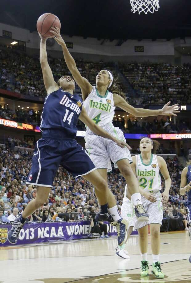 Notre Dame guard Skylar Diggins (4) blocks a shot by Connecticut guard Bria Hartley (14) in the first half of the women's NCAA Final Four college basketball tournament semifinal, Sunday, April 7, 2013, in New Orleans. (AP Photo/Gerald Herbert)