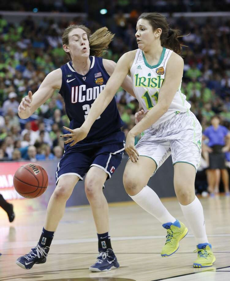 Notre Dame forward Natalie Achonwa (11) passes against Connecticut forward Breanna Stewart (30) in the first half of the women's NCAA Final Four college basketball tournament semifinal, Sunday, April 7, 2013, in New Orleans. (AP Photo/Dave Martin)