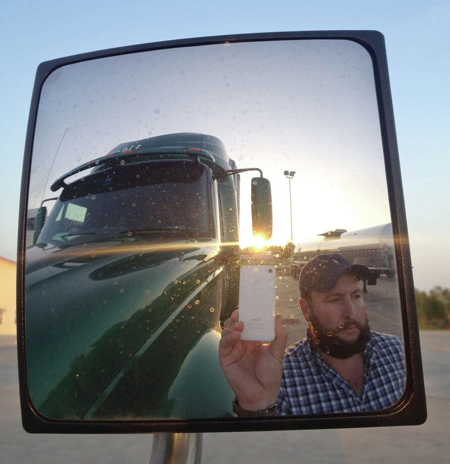"This undated image provided by James Weitze shows a truck driver taking a self portrait on the road. Weitze satisfies his video fix with an iPhone. He sleeps most of the time in his truck, and has no apartment. To be sure, he's an extreme case and probably wouldn't fit into Nielsen's definition of a household in the first place. But he's watching Netflix enough to keep up on shows like ""Weeds,"" ""30 Rock,"" ""Arrested Development,"" ""Breaking Bad,"" ""It's Always Sunny in Philadelphia"" and ""Sons of Anarchy."" (AP Photo/James Weitze) Photo: James Weitze"