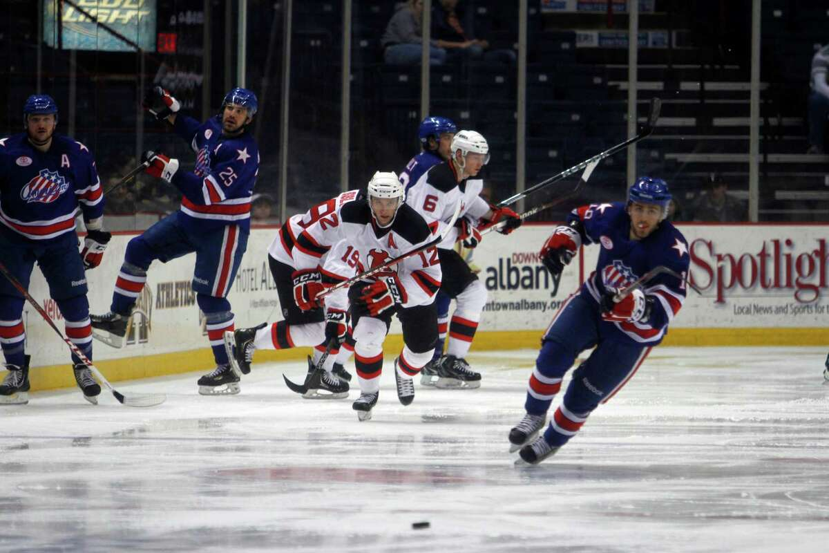 Albany Devil's Tim Sestitio (12), center, and Rochester American's Nick Bailen (16), right, chase down the puck during the game Sunday, April 7, 2012 at the Times Union Center in Albany, N.Y. (Dan Little/ Special to the Times Union)