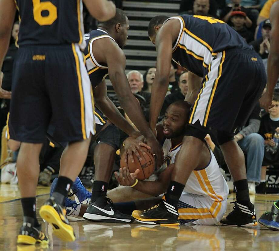 The Warriors' Carl Landry tries to hang on the ball as Jazz players try to wrestle it from him during a game in Oakland, Calif., on Sunday, April 7, 2013. Photo: Mathew Sumner, Special To The Chronicle
