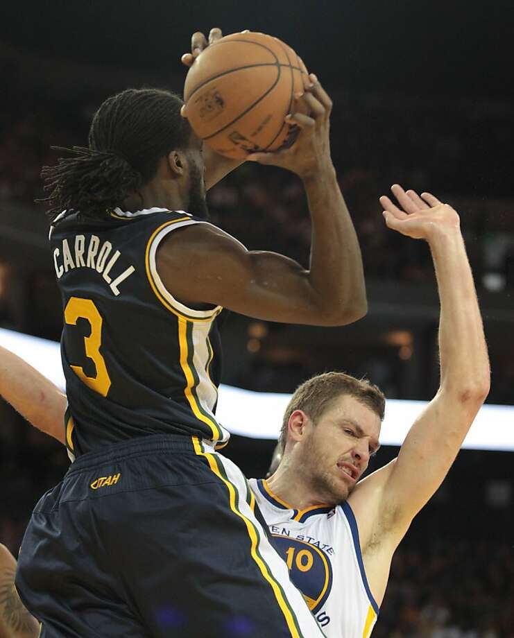 The Warriors' David Lee is knock backwards while the Jazz's DeMarre Carroll gets a rebound during a game in Oakland, Calif., on Sunday, April 7, 2013. Photo: Mathew Sumner, Special To The Chronicle