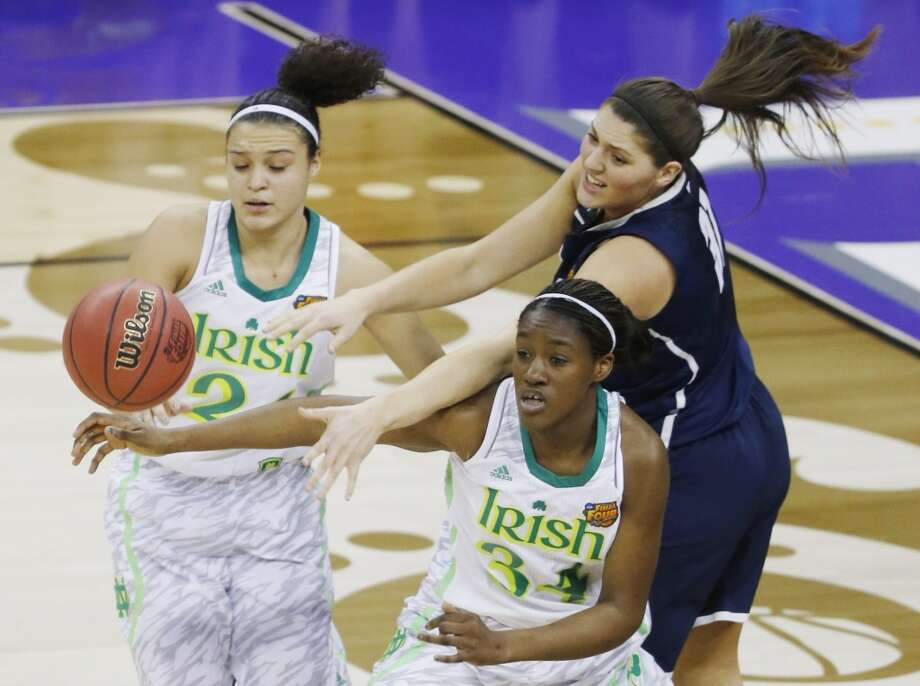 Notre Dame guard Kayla McBride (21), forward Markisha Wright (34) and Connecticut center Stefanie Dolson (31) reach for a loose ball in the first half of the women's NCAA Final Four college basketball tournament semifinal, Sunday, April 7, 2013, in New Orleans. (AP Photo/Bill Haber)