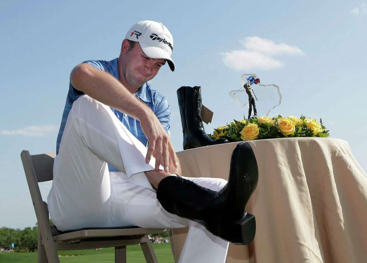 Martin Laird of Scotland adds a pair of cowboy boots to his wardrobe for winning the Texas Open.