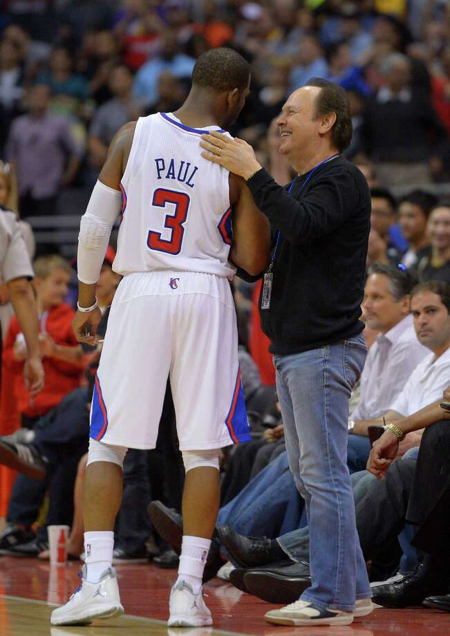 Actor Billy Crystal, who was a Clippers fan even during the team's lengthy down times, congratulates Chris Paul during the closing seconds Sunday. Photo: Mark J. Terrill, STF / AP
