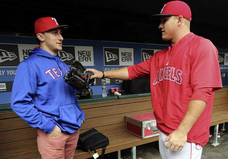 "Johnny Manziel (left) chats with the Angels' Mike Trout. ""I was a little nervous, I'm not going to lie,"" the A&M QB said about throwing out the first pitch before the Rangers-Angels game. Photo: LM Otero / Associated Press"