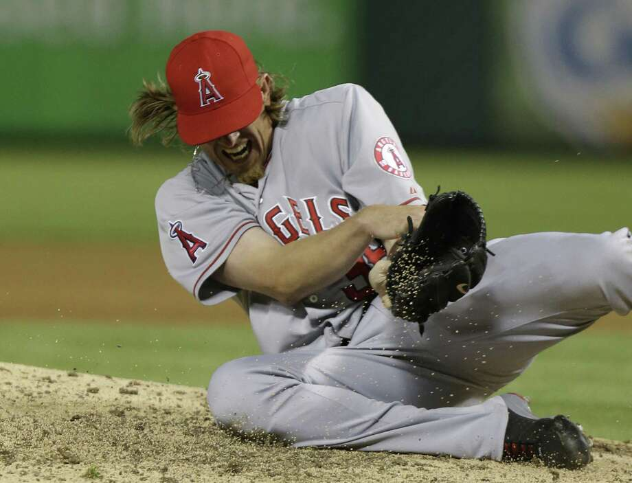 Angels pitcher Jered Weaver holds his left elbow after he awkwardly landed on it to avoid a liner from Mitch Moreland. Photo: LM Otero / Associated Press