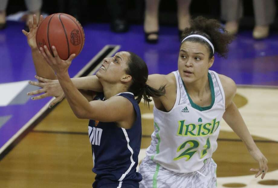Connecticut guard Bria Hartley (14) goes up for a shot against Notre Dame guard Kayla McBride (21) in the second half of the women's NCAA Final Four college basketball tournament semifinal, Sunday, April 7, 2013, in New Orleans. (AP Photo/Bill Haber)
