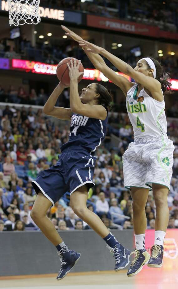 Connecticut guard Bria Hartley (14) goes up for a shot against Notre Dame guard Skylar Diggins (4) in the second half of the women's NCAA Final Four college basketball tournament semifinal, Sunday, April 7, 2013, in New Orleans. (AP Photo/Dave Martin)