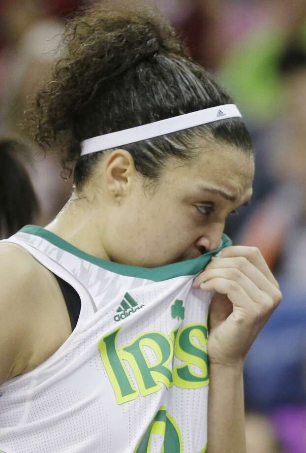 Notre Dame guard Kayla McBride (21) wipes her face in the second half of the women's NCAA Final Four college basketball tournament semifinal against Connecticut, Sunday, April 7, 2013, in New Orleans. UConn won 83-65. (AP Photo/Gerald Herbert)