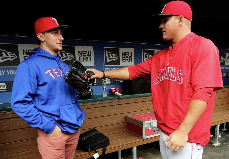 In a meeting of young phenoms, Texas A&M quarterback Johnny Manziel, left, hooks up with Angels left fielder Mike Trout before Sunday night's game at Rangers Ballpark. Photo: LM Otero, STF / AP