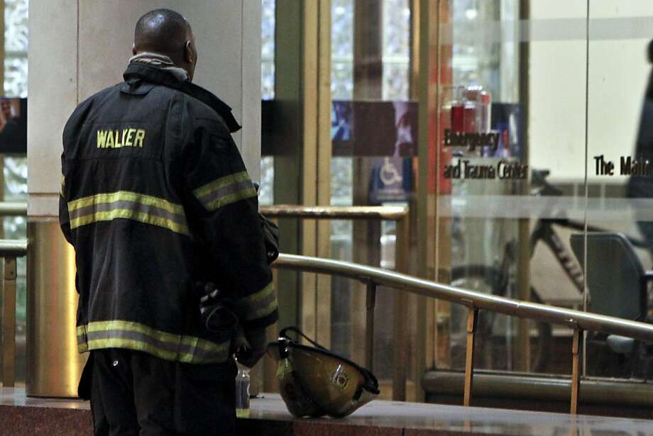 A fireman waits outside the emergency room at Thomas Jefferson Hospital in Philadelphia, Saturday, April 6, 2013, after Capt. Michael Goodwin was brought to the hospital. A fire caused a partial roof collapse that killed Goodwin and injured a colleague who was trying to rescue him, officials said. (AP Photo/ Joseph Kaczmarek) Photo: Joseph Kaczmarek, Associated Press