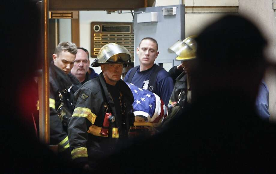 Fellow firefighters carry the body of fallen firefighter Capt. Michael Goodwin at Thomas Jefferson Hospital in Philadelphia, Saturday, April 6, 2013. The fire caused a partial roof collapse that killed Goodwin and injured a colleague who was trying to rescue him, officials said. (AP Photo/ Joseph Kaczmarek) Photo: Joseph Kaczmarek, Associated Press