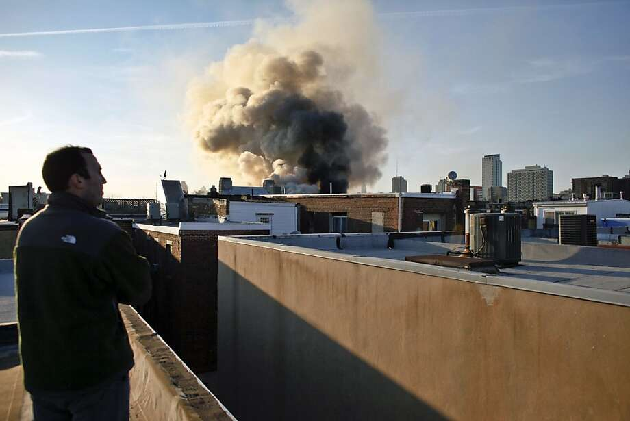 A neighbor watches from a rooftop as firefighters battle a blaze that burned a fabric shop, upstairs apartments and a neighboring boutique in Philadelphia, Saturday, April 6, 2013. The fire caused a partial roof collapse that killed a firefighter and injured a colleague who was trying to rescue him, officials said. (AP Photo/ Joseph Kaczmarek) Photo: Joseph Kaczmarek, Associated Press