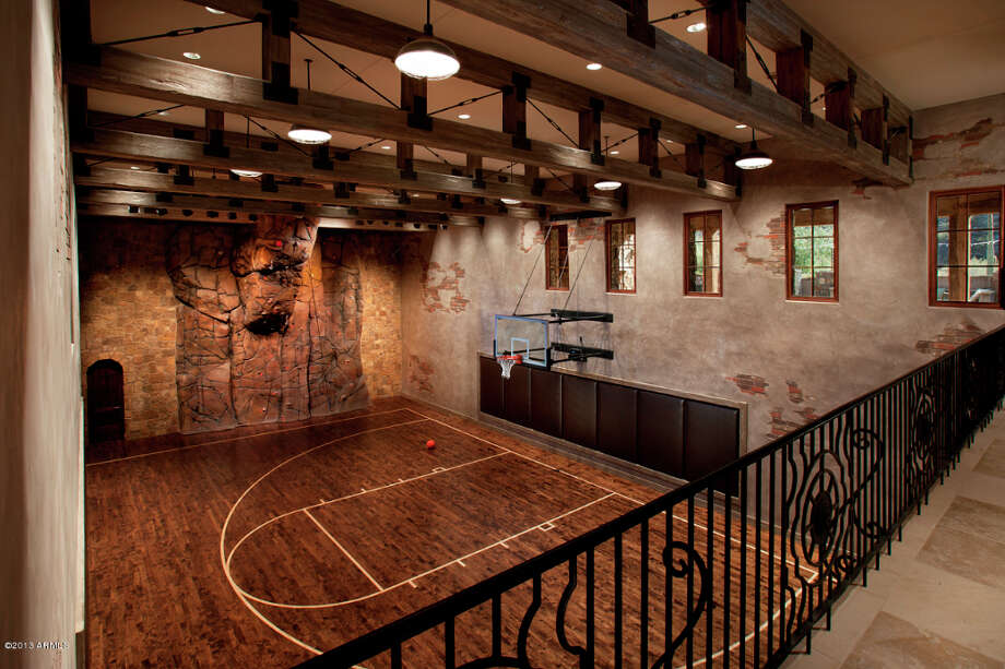 In addition to outdoor pool, outdoor entertaining areas, home theatre, etc., the wooden indoor basketball court looks like a fun area for a quick game of pick up.