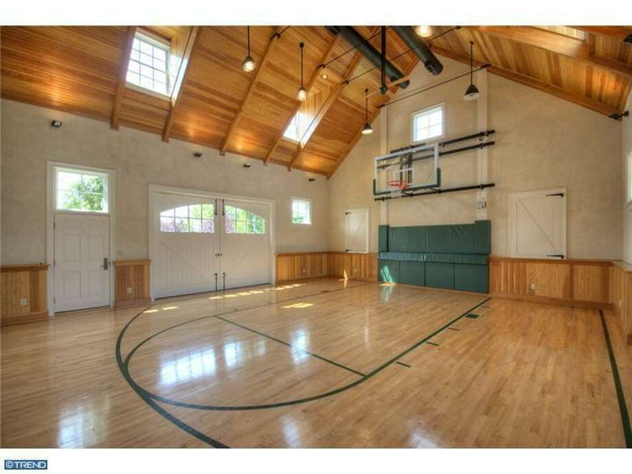 Home has 7 bedrooms, 4 full and 4 half baths.  Multiple entertaining areas, include billiards, home theatre, bowling alley and this light filled basketball court.