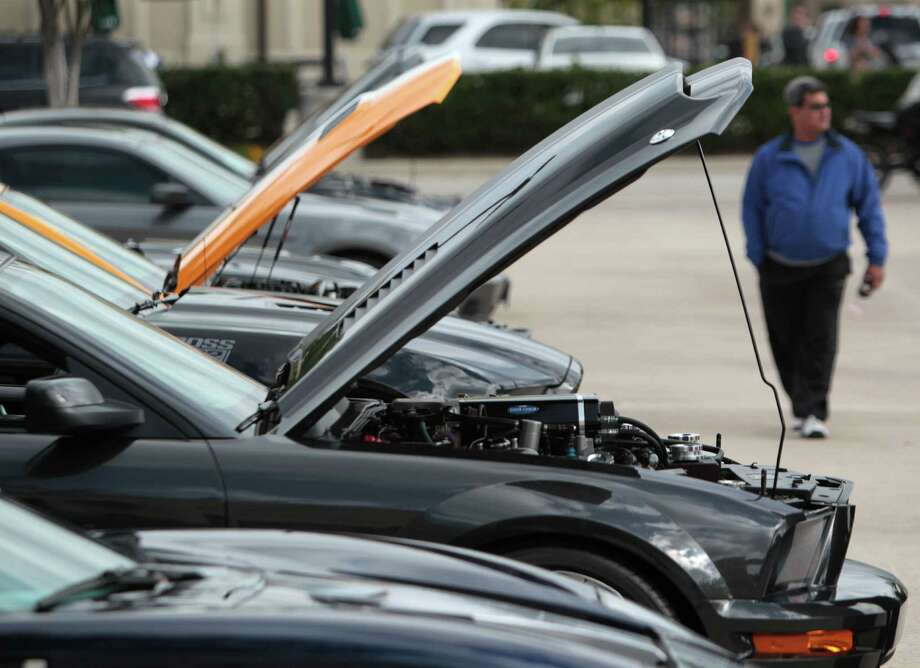 Sports car enthusiasts view vehicles on display while attending the Coffee and Cars' at Vintage Park on Saturday, April 6, 2013, in Houston. Photo: Mayra Beltran, Houston Chronicle / © 2013 Houston Chronicle