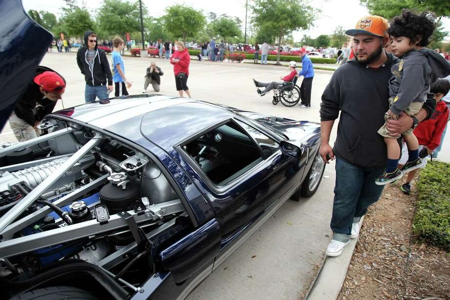 Oscar Ramirez carries son Kaleb Ramirez, 3, while walking through the Coffee and Cars autoshow at Vintage Park on Saturday, April 6, 2013, in Houston. Photo: Mayra Beltran, Houston Chronicle / © 2013 Houston Chronicle