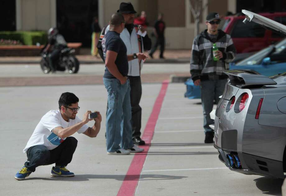 Jorge Ramirez photographs a sports car during the Coffee and Cars auto show at Vintage Park on Saturday, April 6, 2013, in Houston. Photo: Mayra Beltran, Houston Chronicle / © 2013 Houston Chronicle
