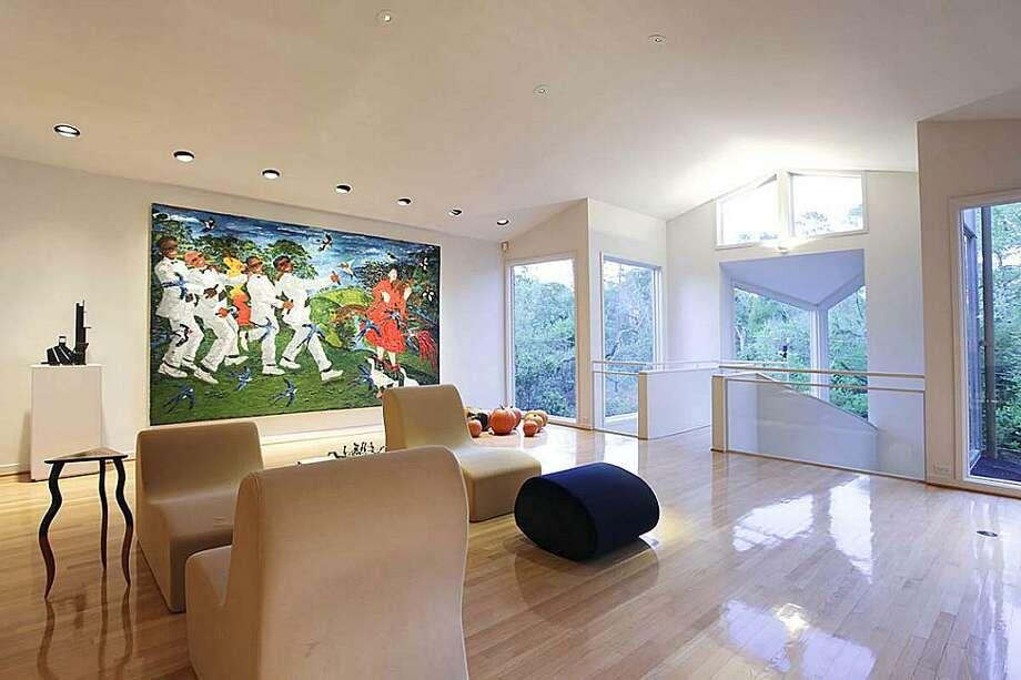 Formal living room. Hardwood floor. Floor to ceiling windows with bayou views. Photo: Greenwood King Properties
