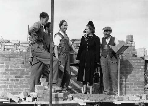 British Conservative Party candidate for Dartford, Margaret Roberts (later Margaret Thatcher) with foreman bricklayer John Hayes during a canvassing tour of the constituency, 13th October 1951. The men are working on the Temple Hill Estate. Photo: Keystone, File / 2009 Getty Images