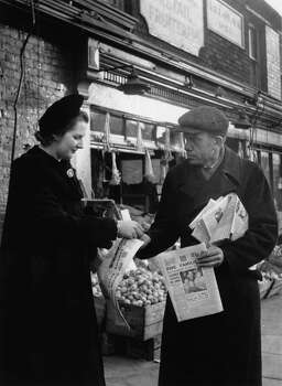 British Conservative Party candidate for Dartford, Margaret Roberts (later Margaret Thatcher) buys a copy of The Evening News from a street vendor during a tour of the constituency, 24th January 1950. Photo: Chris Ware, File / 2009 Getty Images