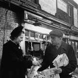 British Conservative Party candidate for Dartford, Margaret Roberts (later Margaret Thatcher) buys a copy of The Evening News from a street vendor during a tour of the constituency, 24th January 1950.