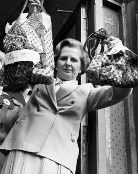 Margaret Thatcher holds up shopping bags to show the price difference in 1979. Photo: Manchester Daily Express, File / SSPL/Manchester Daily Express
