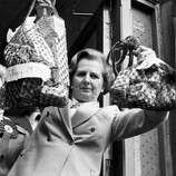 Margaret Thatcher holds up shopping bags to show the price difference in 1979.