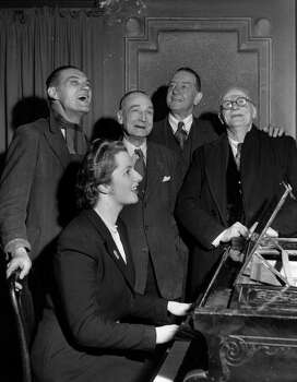 Conservative candidate Margaret Roberts accompanies four voters on the piano in a sing-song after a brief political argument in the bar of The Bull Inn in 1950. Photo: Keystone, File / Hulton Archive